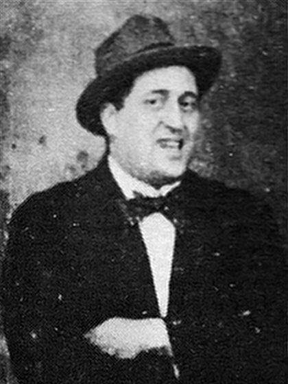 A man in a suit, with a hat, and a bow -tie. He is smiling.