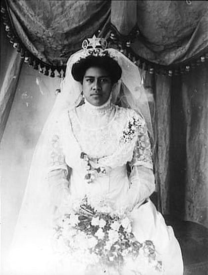 Picture of a young African woman wearing a white, elaborate wedding dress with a veil.