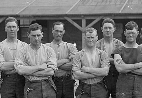 Eight young, strong soldiers wearing casual clothes stand in a yard with their arms crossed.
