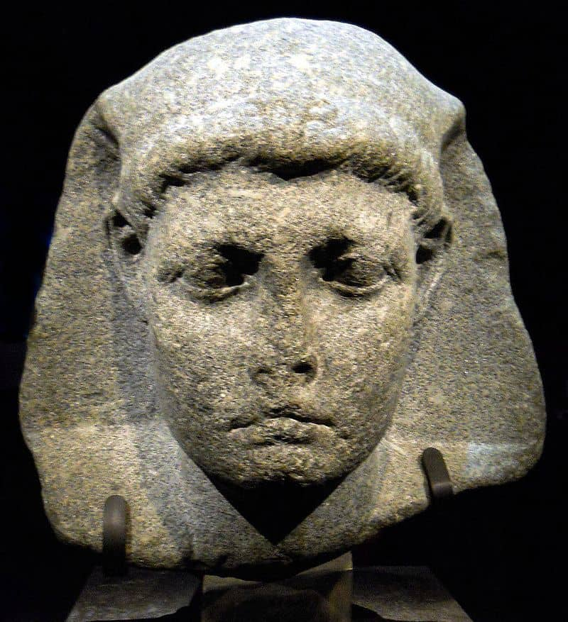 An Egyptian-style stone sculpture. It is the head of a young man. He wears the royal Egyptian headdress, his forehead is wide, short, and flat. He has arched eyebrows, big eyes, somewhat high cheekbones, a smallish mouth, and a rounded chin.