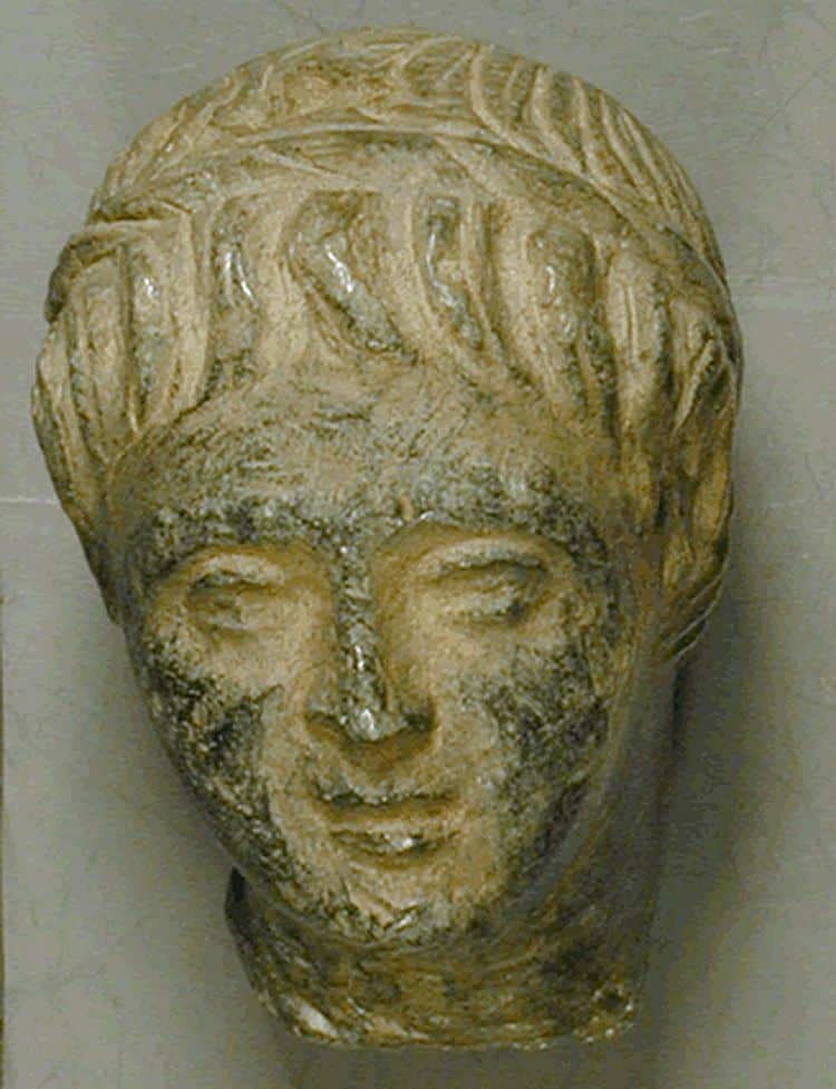 A more delicately carved head. It also shows a young man. He has long hair that falls on his forehead. He has arched eyebrows, biggish eyes, a smallish, straight nose, a small mouth, and a rounded chin.