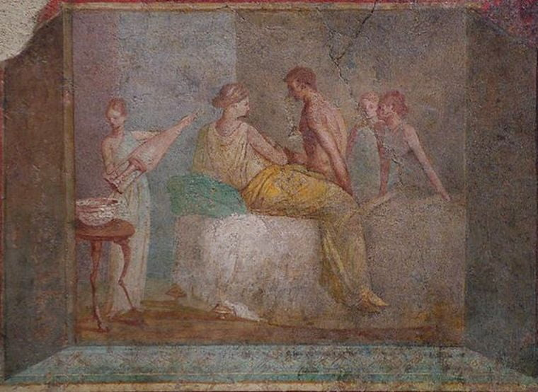 An indoor scene. Inside a bedroom. A couple sits on their bed close to each other. He is undressed. There are three slaves in the background carrying on their duties.