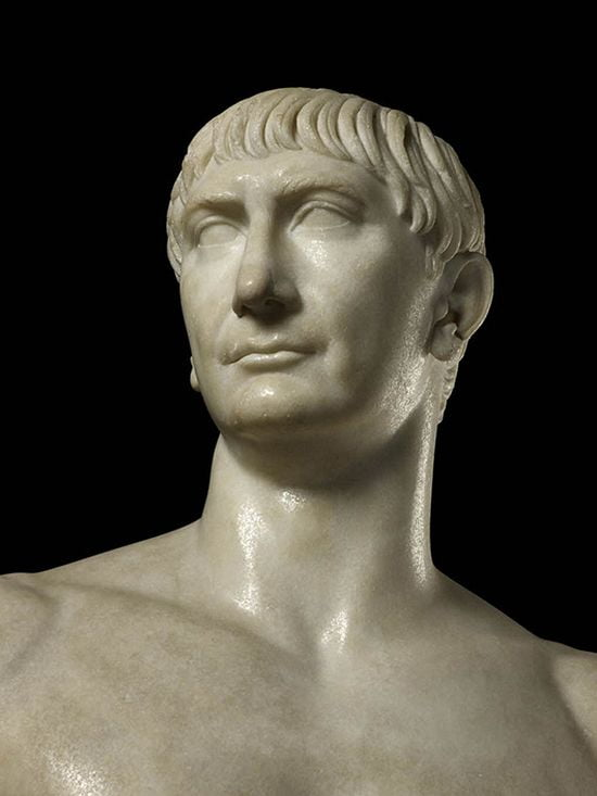 Marble statue of a middle-aged man. His hair is straight and he has a fringe that covers half his forehead. His face seems to be rectangular with a slightly narrower jaw than forehead. He has marked eyebrows, somewhat deep-set eyes, a very long, straight nose, a medium-sized mouth with thin lips, and a strong jaw.