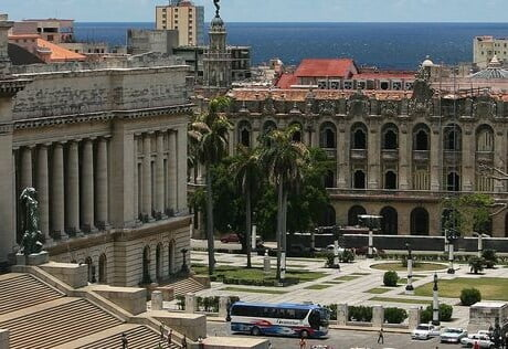 A large, monumental city square. It is surrounded by European-style buildings. The ocean is in the background.