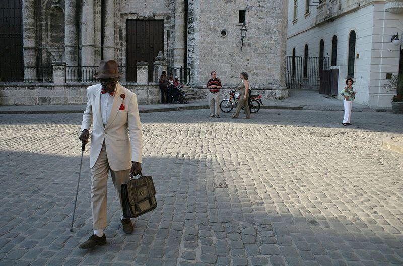 A man walks on a cobbled street.
