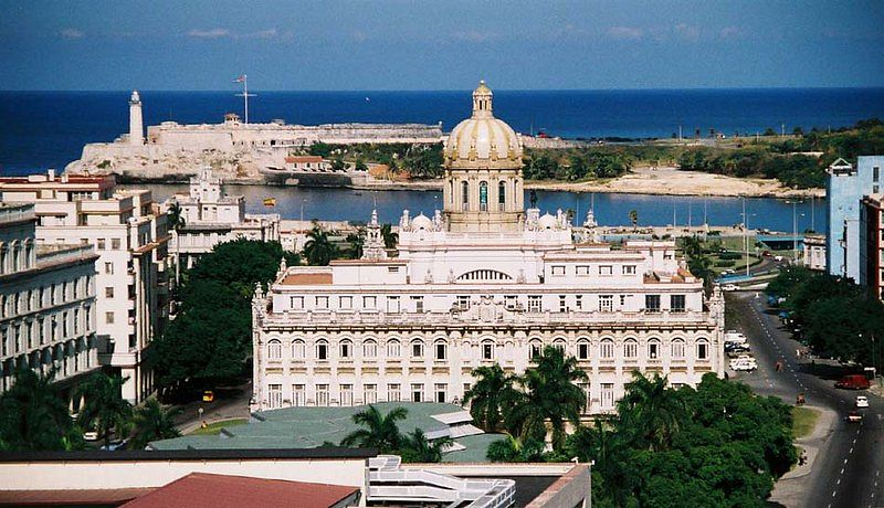 Aerial view of a city. It is surrounded by the sea. In the foreground, there is a big, white, neoclassical building.