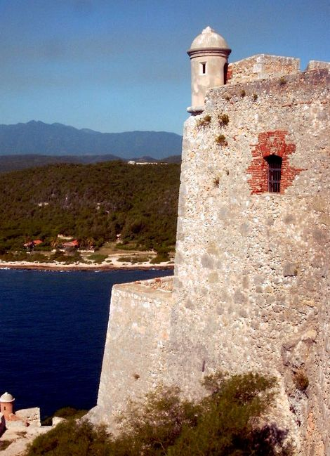 On the right is the massive and tall, stone tower of a fortress. It looks over the bay, to the sea and a stretch of land.