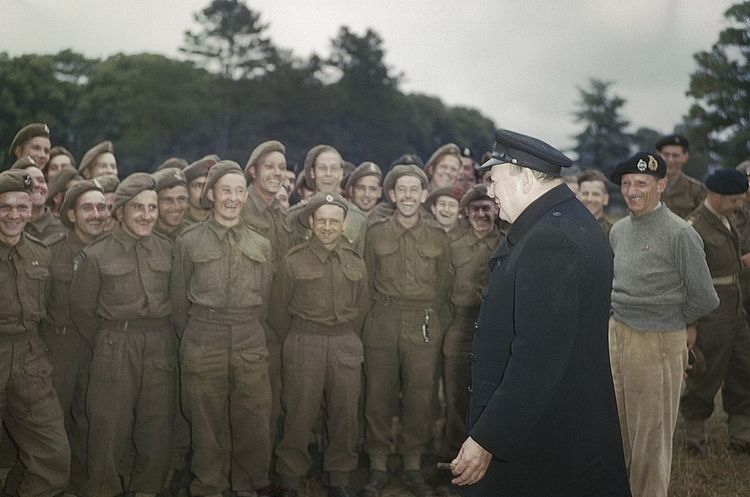 An older Winston adresses a group of soldiers who are laughing.