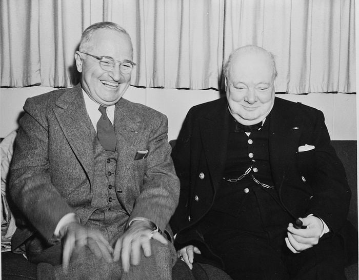 Two older men laughing heartedly. They are wearing elegant suits.