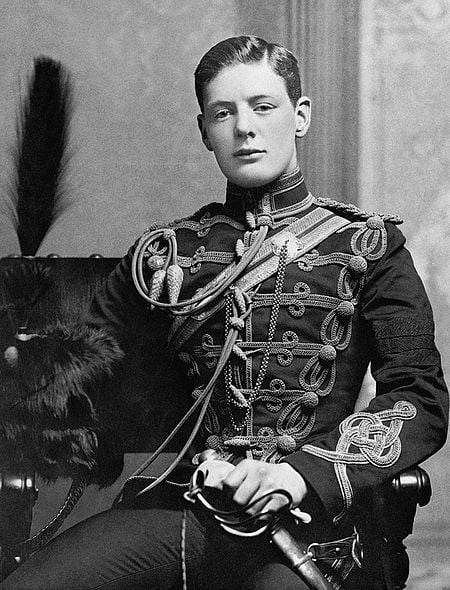 A dashing young man, probably in his late teens. He is wearing full ceremonial military uniform with sword included. He is sitting on a chair and looking directly at the camera. He is slim and has classical features.