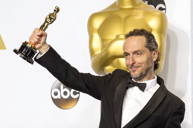 Photo of Emmanuel Lubezki backstage at the Oscars. He is holding an Oscar in his hand.