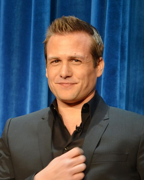 Photo of Gabriel Macht. He is at a press conference, wearing a gray suit. He has light brown hair, he is tanned, he has small eyes, and a strong jaw.