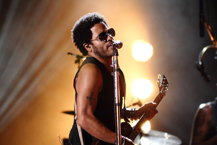 Photo of Lenny Kravitz playing guitar and singing on stage.