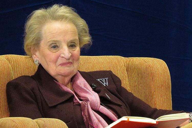 Photo of Madeleine Albright. She is sitting on a couch and holding a book.