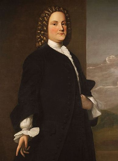 An even younger Benjamin, perhaps in his thirties. He is standing. He wears an elegant black suit with a white puffy shirt underneath. He is wearing a long, brown, curly wig. He has brown eyes.