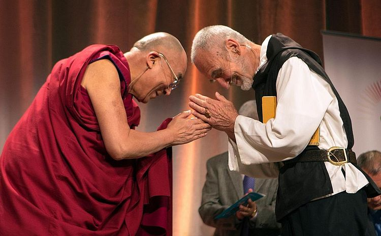 The Dalai and another man on a stage. The other man, too, is wearing traditional clothes, but they are probably European. Both men are bowing down in a sign of respect for each other. Both have their hands in prayer.