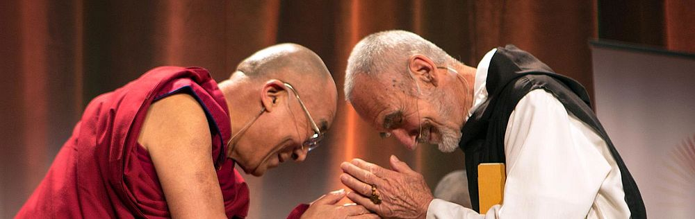 The Dali Lama and another man bow towards each other smiling in a gesture of respect.