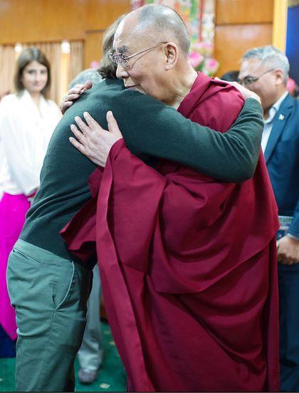 The Dalai hugs a man.