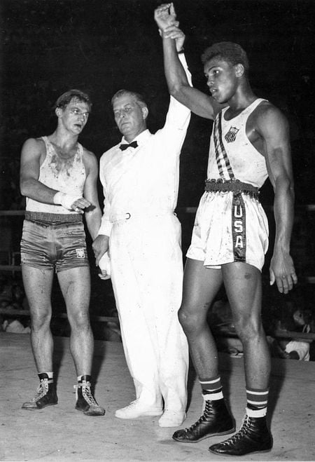 The referee and two young boxers. The referee is raising Muhammad Ali's arm, meaning Ali has won the match.