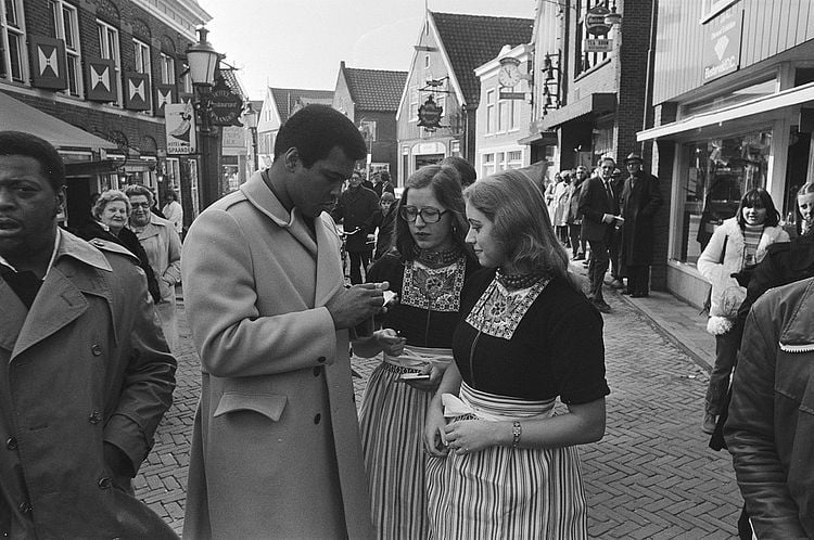 Muhammad, elegantly dressed, signs autographs for two young women. They are in the middle of a European street and other people have stopped to watch him.
