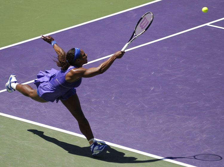Serena on the tennis court. She is running desperately to get to a ball.