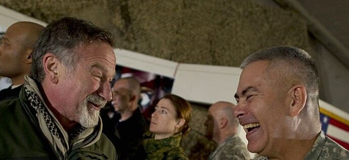 Robin Williams and another man are inside a military base. Robin is saying something to the officer and making him laugh.